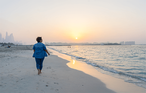 alcoholic woman walking along the sandy beach during sunset while following the 12 step program