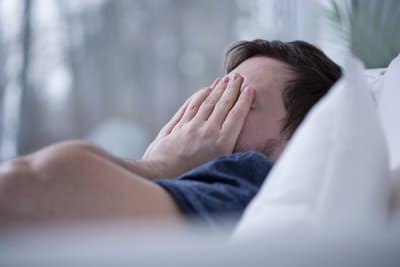 man laying in bed with insomnia due to prolonged drug abuse