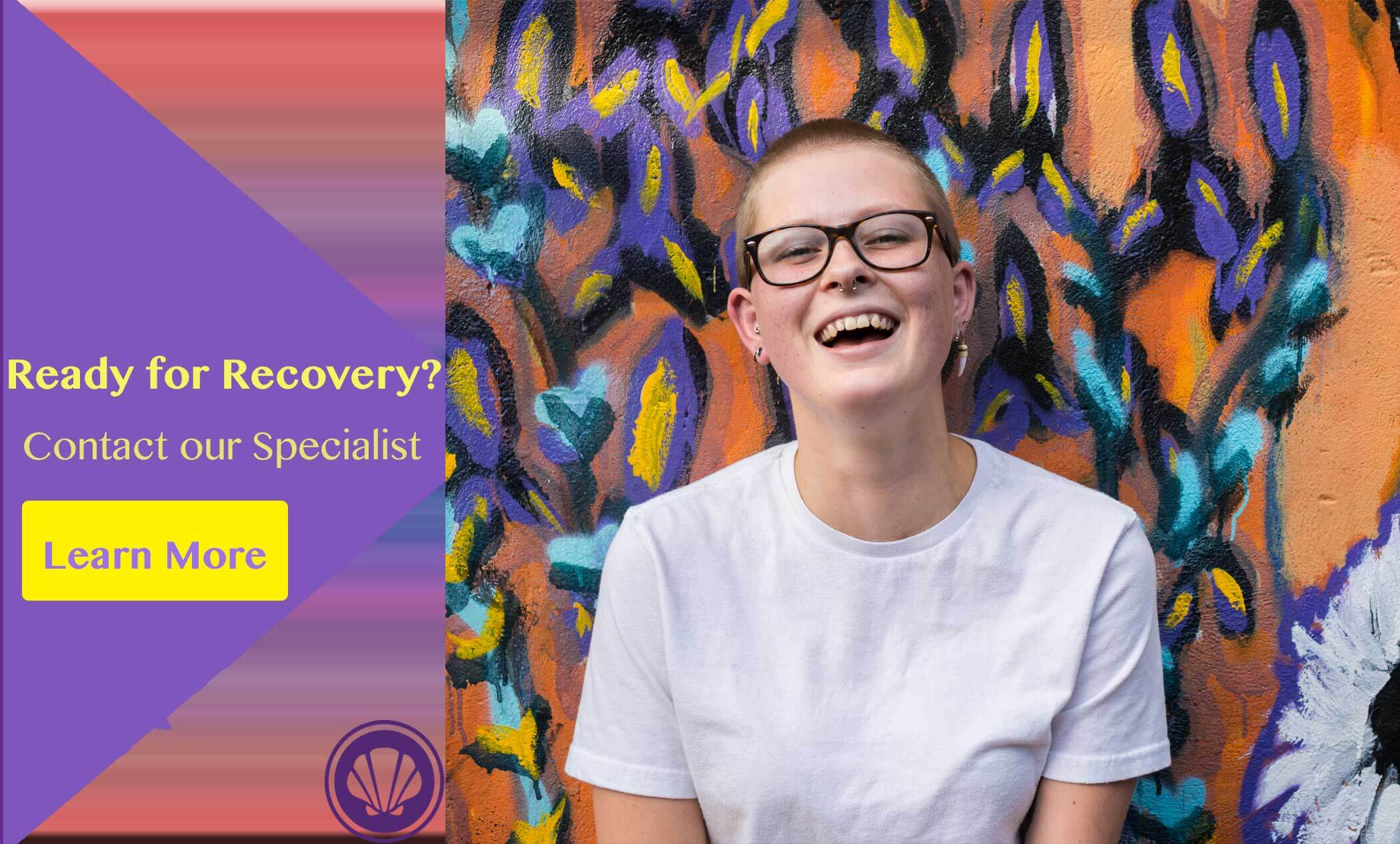 lgbtq female smiling infront of a colorful wall with yellow text beside her that reads ready for recovery? contact our specialist and learn more.
