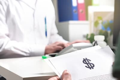 Patient holding paper document, insurance, bill or invoice with dollar sign in doctor office in hospital or emergency room
