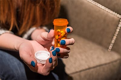 closeup of girls hands holding an open pills bottle with pills in it