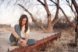 Native American man sitting on curb
